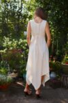 Cream-colored dress with asymmetrical cutting in 2 thin cotton layers. Tie straps and buttons.
