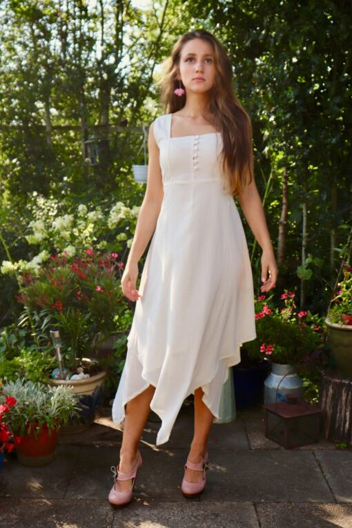 Elegant cream-colored dress with buttons at the chest. 2 thin layers in soft natural cotton and a trendy asymmetrical cutting.