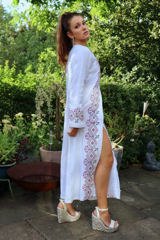 Ethnic caftan dress in white with colorful embroidery at the sleeves and in the front. Opens with buttons all the way down