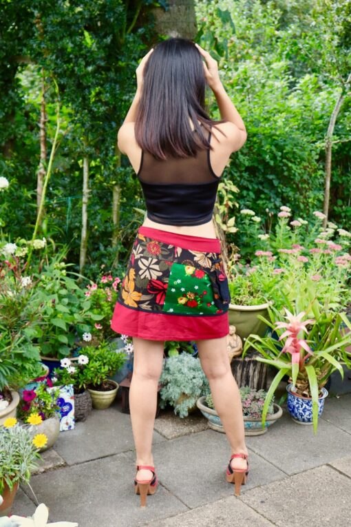 Trendy mini skirt in red with colorful patterns. Onesize wrap skirt with pcokets