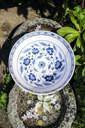 Ceramic bowl from the top with floral blue motifs on a white backdrop