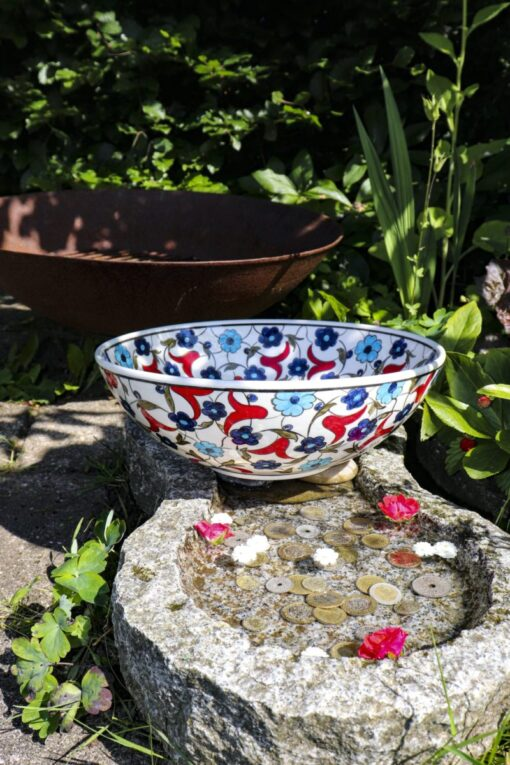Colorful ceramic bowl in Ottoman style design with bright blue and red colored flowers on a white backdrop. Lead free and ideal for serving fruits and salads.