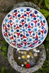 Handmade ceramic fruit bowl with vibrant blue, red and white colored flowers on a white backdrop. Ottoman style design