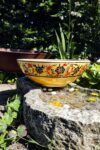 Colorful ceramic bowl in warm yellow with floral motifs. Lead free and handmade quality