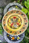 Yellow ceramic bowl with motifs of red, black flowers, interior decorated. For fruits and salads