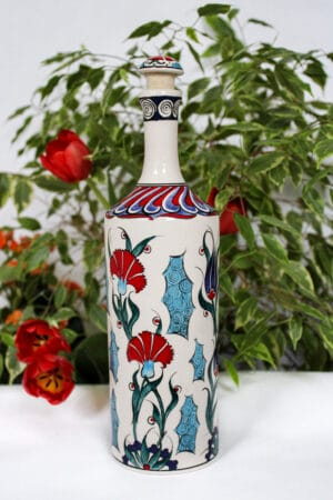 Handmade ceramic oil bottle decorated with bright illustrations of tulips and carnations in blue and red colors