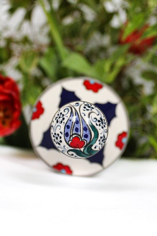 The handpainted lid to a ceramic bottle, decorated with tulips and flowers