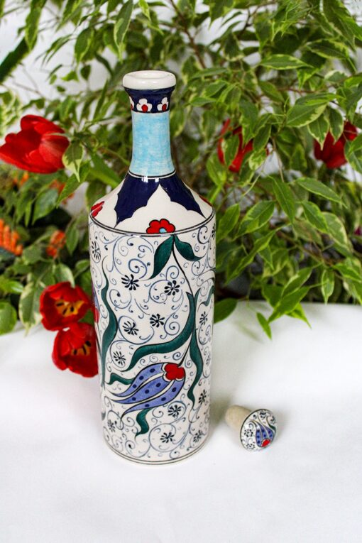Keramik flaske med farverige blomstermotiver af tulipaner. Røde, blå og grønne farvenuancer på en hvid baggrund.Blyfri