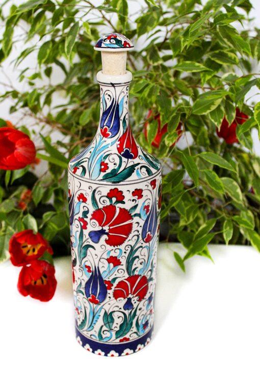 Håndlavet farverig keramik flaske med motiver af nelliker og tulipaner i røde, blå, turkise og grønne farver. Håndmalet låg