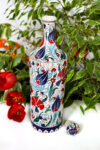 Decorative ceramic bottle suited for food ware. Beautifully illustrated with red and blue flowers. Foodsafe quality
