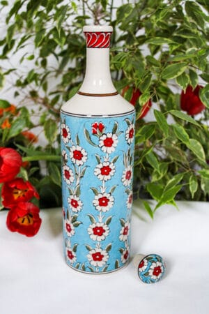 Handmade ceramic oil bottle in turquoise, with red and white floral motifs