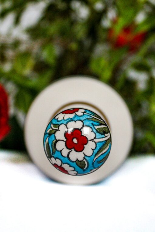 Handpainted floral lid on a handmade ceramic bottle with flowers