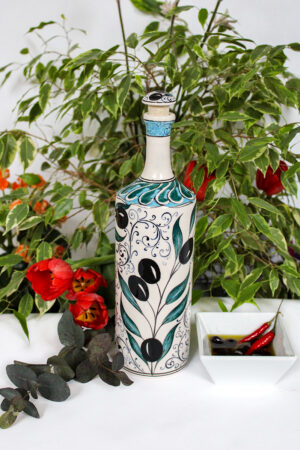 30 cm unique olive oil bottle in handmade ceramics. Decorated with olive motifs in black, green and turquoise.White backdrop.