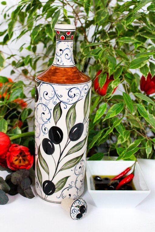 Keramisk oliven olie flaske illustreret med motiver af olivengrene i sorte, grønne og brune nuancer og håndmalet låg.