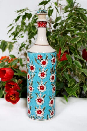 Ceramic bottle with colorful flowers in red and white on a turquoise background. Handpainted lid