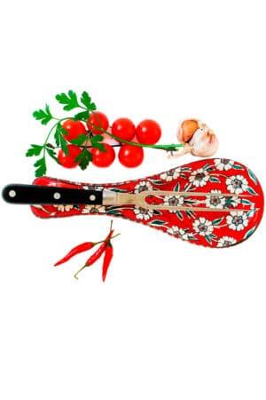 Flot keramisk skeholder i rød med hvide blomstermotiver, til at lægge bestik og køkkenredskaber på under madlavningen.