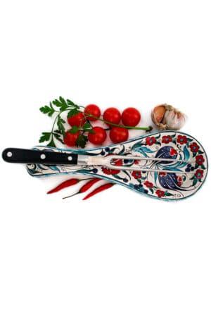 Farverig håndlavet skeholder der kan bruges til at lægge dit køkkenbestik på under madlavning og servering. Hvid med blå, røde og turkise blomstermotiver. Kan vaskes i opvaskemaskine.