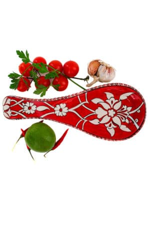 Trendy spoon rest perfect to keep your kitchen counter clean during cooking. Handmade ceramic in a warm red color with a white floral motif