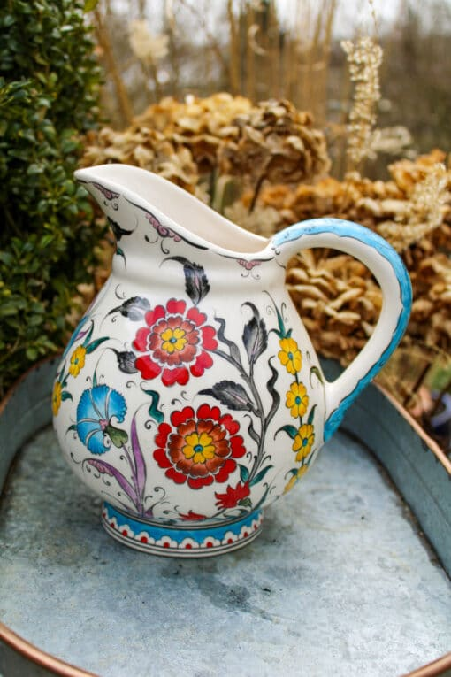 Handmade ceramic jug with a handle and floral motifs