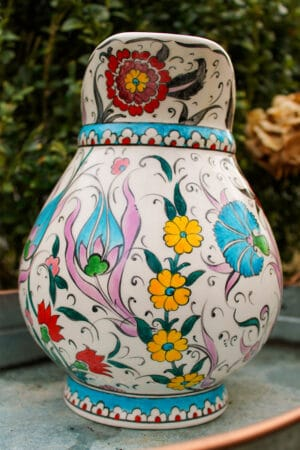 Ceramic jug with beautiful flower motifs in yellow, red, turquoise and blue colors. Floral wreath