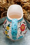 Handmade ceramic jug with a floral wreath, handle and flowerdecorations. Chubby design
