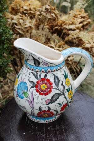 Handmade ceramic jug with a floral wreath and flower motifs