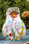 Handmade ceramic jug with flower decorations in red, green and yellow