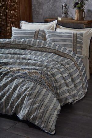 Etnisk sengetøj i eksklusiv økologisk bomuld med mønstre og striber i blå,sorte og gyldne farver på en hvid baggrund. Til dobbeltdyne med lagen og 4 pudebetræk . 2 i hvid