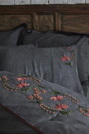 Håndlavede blomsterbroderier i røde, rosa og grønne farver som dekoration på luksuriøst antracitgråt økologisk sengetøj