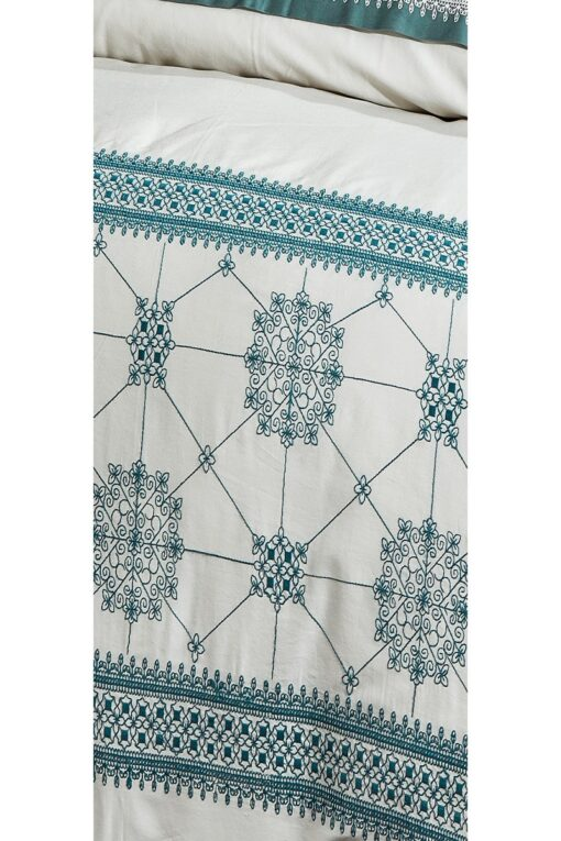 Organic bed linen with embroideries and motifs in blue green colors . Flowers and geometrical forms