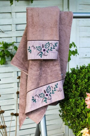 Luxurious organic towel set in dusty rose with handmade floral embroidery at the border