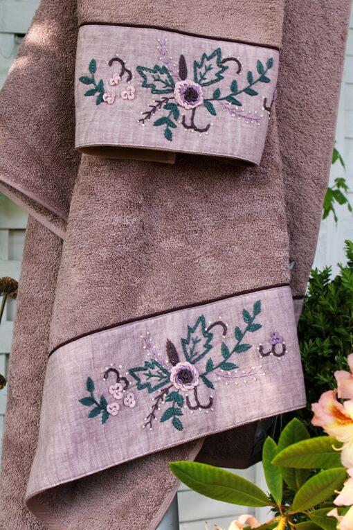 Håndlavet broderi i støvede grønne, rosa og mørkrosa farver på et økologisk rosa håndklædesæt