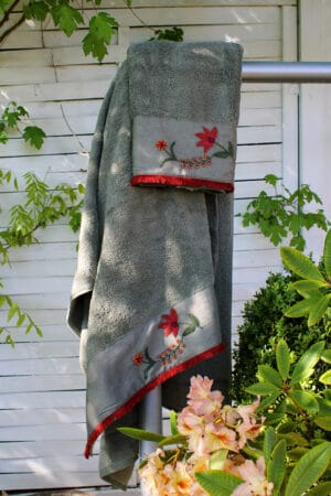 Luxurious towel set in olive green with a handembroidered border decorated with red floral motifs