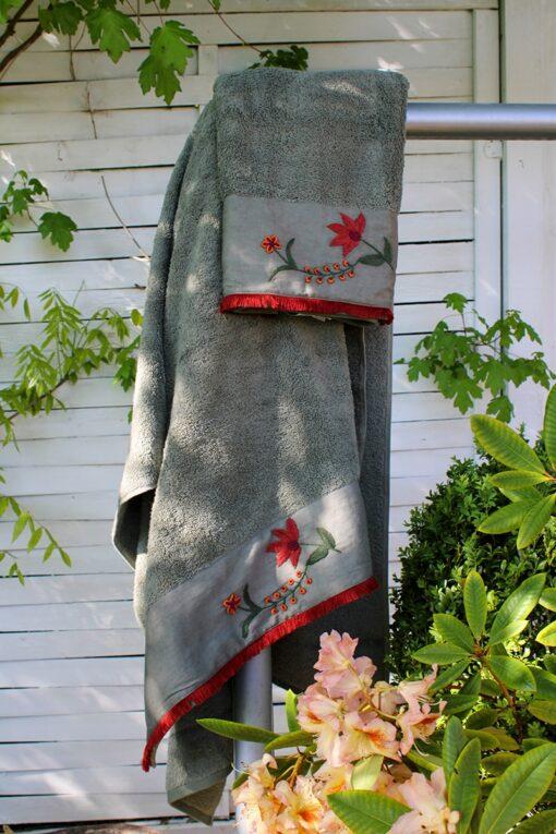 Elegant oliven grønt håndklædesæt med en bort med skønne røde håndlavede blomsterbroderier forneden