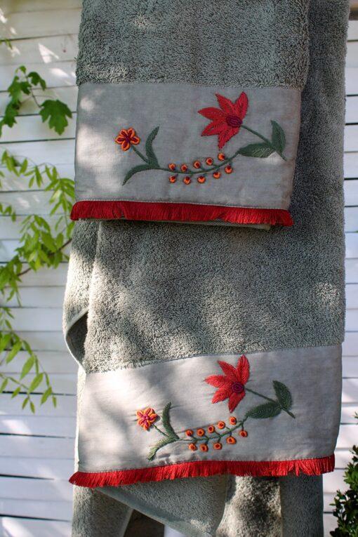 Håndlavet blomsterbroderi i rødlige farver på økologisk støvet grønt håndklædesæt i økologisk bomuld