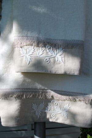Elegant broderi på khakifarvet bort af et tykt lyst håndklædesæt i økologisk bomuld