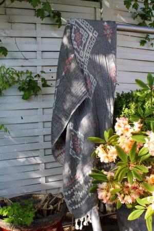 Elegant Tyrkisk hammam håndklæde - peshtemal i økologisk bomuld. Lysegråt med geometriske mønstre i støvede hvide, røde og grønlige farver