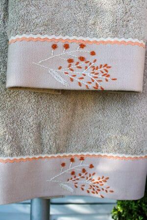 Enkle organiske håndlavede broderier i støvet orange på en naturfarvet bort forneden på et beige håndklædesæt