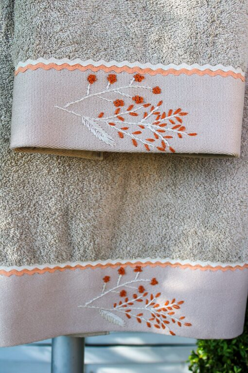 Organic dusty orange embroideries decorating a beige colored towel set