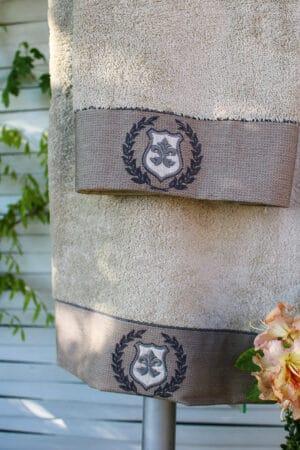 Håndbroderede motiver på en bort forneden på et økologisk bomulds håndklæde i beige