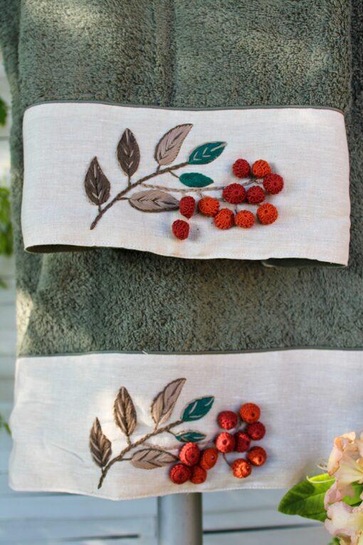 Håndlavet broderi med elegante røde pomponer i rødlige nuancer der dekorerer et støvet grønt unikt håndklædesæt