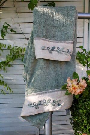 Håndklædesæt i økologisk bomuld i en lys støvet grøn med flot håndbroderert bort forneden